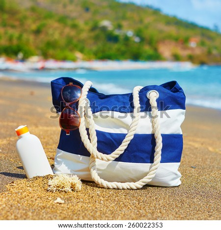 Beach bag, sunscreen bottle and sunglasses on a Balinese beach - stock photo