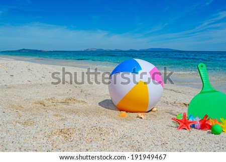 beach ball and rackets on a golden shore - stock photo