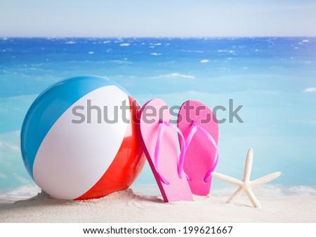 Beach ball, flip flops, starfish on sandy beach against blue ocean - stock photo