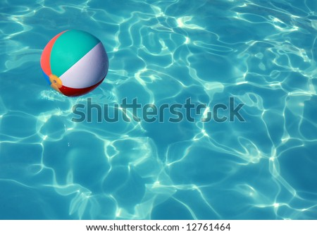 Beach Ball in Pool with sun reflection - stock photo