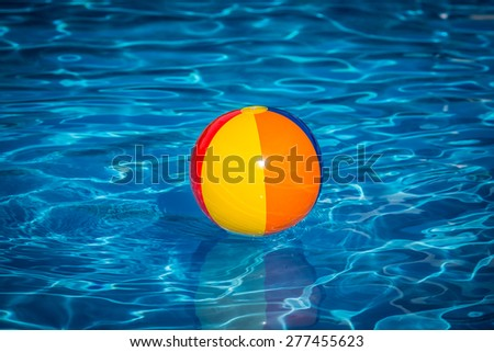 Beach ball in swimming pool. Summer vacation concept - stock photo