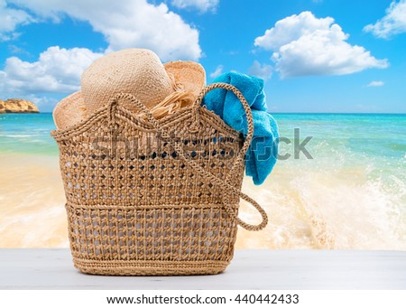 Beach basket packed with towel and sunhat with beach blur background - stock photo