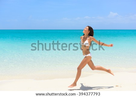 Beach bikini woman carefree running in freedom fun. Joyful happy Asian girl relaxing showing joy and happiness in slim body for weight loss diet concept on perfect white sand. - stock photo