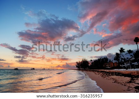 Beach, boats and hotel, at sunset - stock photo