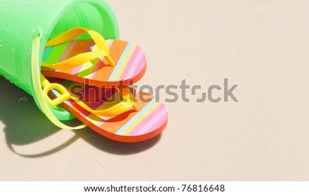 beach bucket and flip flops with copyspace - stock photo