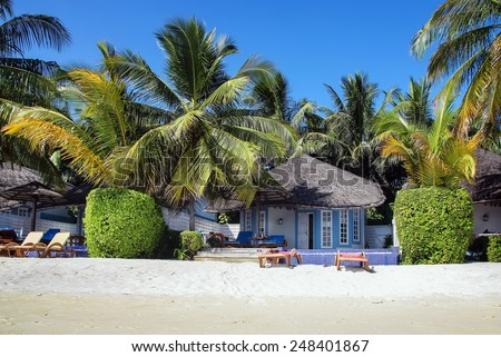 Beach bungalows with deck chairs on a tropical island, Maldives - stock photo