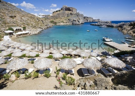 Beach by Saint Paul Bay in Lindos, ruins of Acropolis in the background, Rhodes, Greece - stock photo
