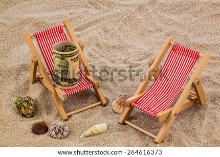 beach chair with dollars on the sandy beach. symbolic photo for cost of travel, vacation, holidays. save on vacation - stock photo