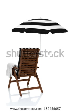 Beach chair with umbrella and towel angled behind view - stock photo