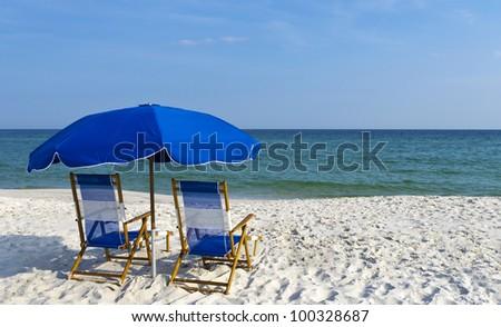 Beach chairs and an umbrella on the gulf coast. - stock photo