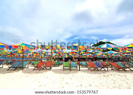 Beach chairs and colorful umbrella on the beach in sunny day, Phuket Thailand - stock photo