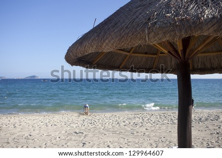 Beach Chairs and Umbrella on a beautiful island, panoramic view with much copy space - stock photo