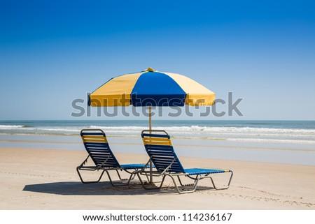 Beach Chairs and Umbrella on an Empty Ocean Beach in Florida - stock photo