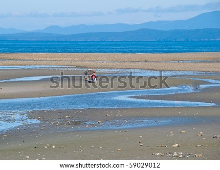 Beach chairs and umbrella on the ocean shore at low tide. - stock photo