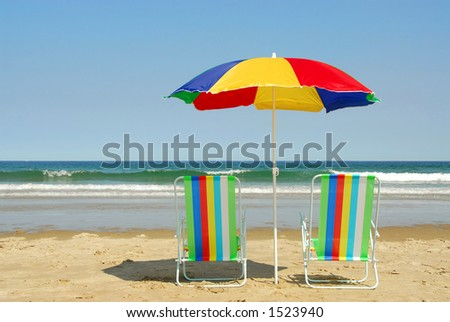 Beach chairs and umbrella on the ocean shore with surf in the background, horizontal - stock photo