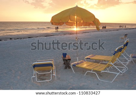 Beach chairs and umbrellas at sunset, Clearwater, Florida. - stock photo