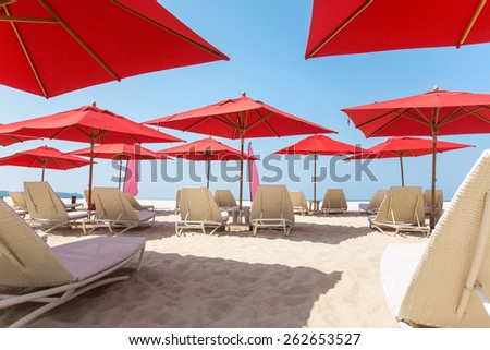 Beach chairs and umbrellas on a sand beach - stock photo