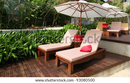 Beach chairs and white umbrella. - stock photo