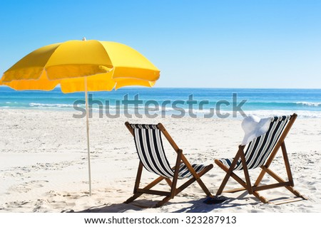 Beach chairs and yellow umbrella in sand with bright sunlight  - stock photo