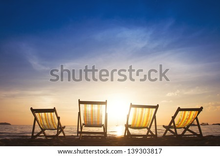 beach chairs at sunset, group tours - stock photo