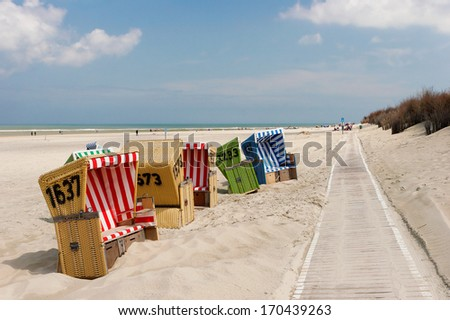 Beach chairs on Langeoog islands coast in Germany - stock photo