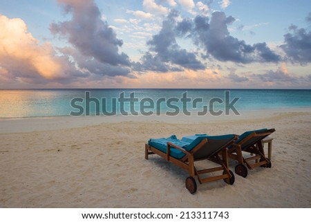 Beach chairs on the beach at sunset - stock photo