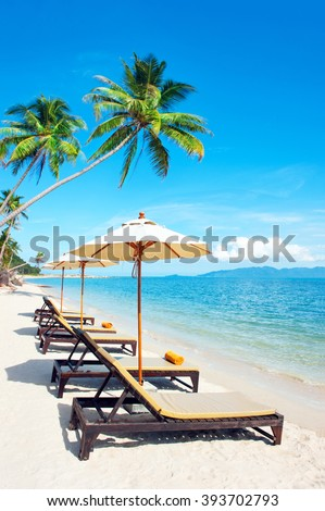 Beach chairs on the white sand beach with cloudy blue sky and su - stock photo