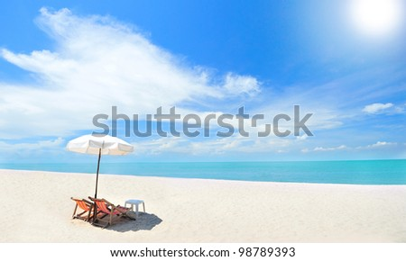 Beach chairs on the white sand beach with cloudy sky and sun - stock photo