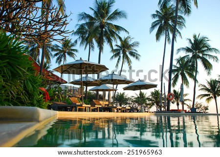 Beach chairs with umbrella beside swimming pool  - stock photo