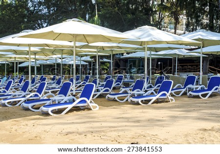 Beach chairs with umbrella on the sand - stock photo