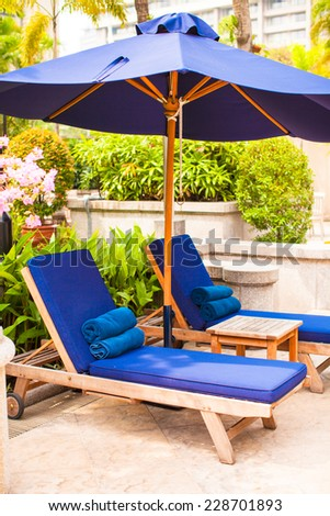 Beach chairs with umbrellas in exotic resort near swimming pool - stock photo