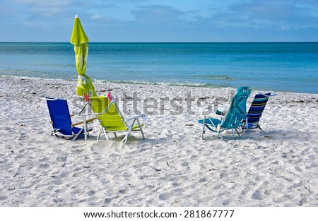 Beach Chairs with Umbrellas on the Beach - stock photo