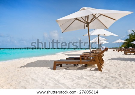 beach chairs with white umbrella at the ocean front - stock photo