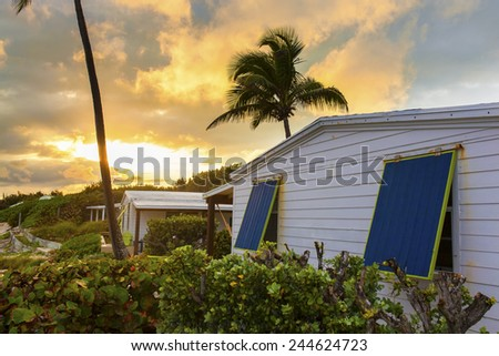 beach cottage in the tropics with perfect sunset - stock photo