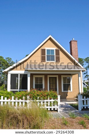 Beach Cottage with a White Fence - stock photo