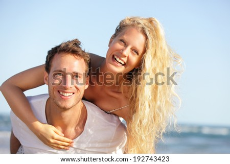 Beach couple fun - lovers on romantic travel doing piggyback in love on honeymoon vacation summer holidays romance. Young happy people, Caucasian woman and man embracing outdoors, - stock photo