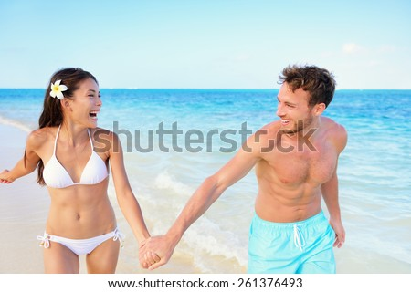 Beach couple having fun happy on beach vacation during summer holiday. Multiracial fit couple running together holding hands laughing in the sun. Young adults in shape carefree happiness. - stock photo