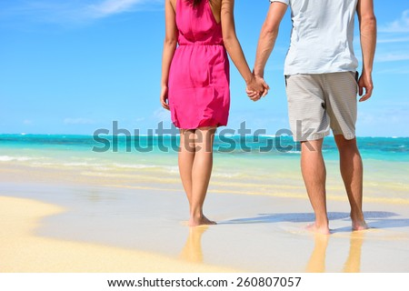 Beach couple in love holding hands on honeymoon. Lower body crop showing pink dress, casual beachwear, legs and feet of romantic newlyweds people standing on white sand on travel summer vacations. - stock photo