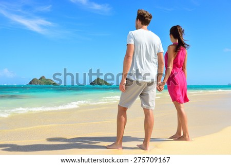 Beach couple looking at ocean view from behind. Couple standing on white sand in pink dress and beachwear on vacations on Lanikai beach, Oahu, Hawaii, USA with Na Mokulua Islands. - stock photo