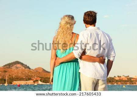 Beach couple romantic at sunset embracing walking by ocean sea. Beautiful casual young couple enjoying view with back at rear view. Summer vacation travel in Majorca, Balearic Islands, Spain. - stock photo