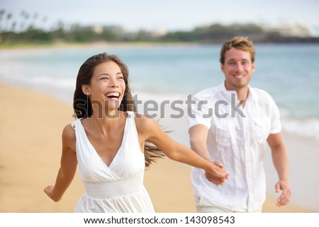 Beach couple running having fun laughing together during summer travel vacation holiday on beautiful golden beach. Joyful excited multi-ethnic couple, Asian woman and Caucasian man. - stock photo