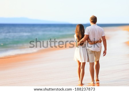 Beach couple walking on romantic travel honeymoon vacation summer holidays romance. Back rear view of casual young happy lovers in full body length on beach. - stock photo