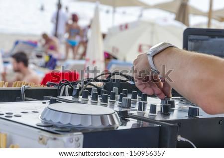 Beach Dj close-up. Summer beach club dj makes party fun for visitors sunbathing - stock photo