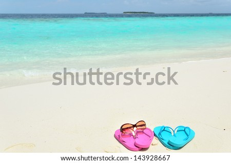 Beach flip-flops and sunglasses on tropical beach -- vacation concept - stock photo