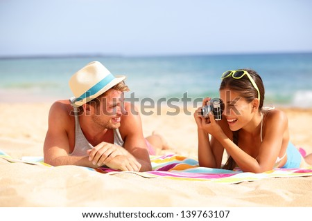 Beach fun couple travel. Woman taking photo picture of man smiling happy with retro vintage camera, Cool trendy modern hipster interracial couple on summer holidays vacation on tropical beach. - stock photo