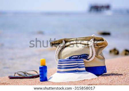 Beach gear on the sand overlooking the sea with a sunhat, sunscreen, slip slops and beach bag conceptual of a summer vacation in the tropics - stock photo