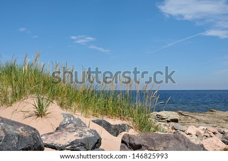 Beach grass, rocks, and sand at a beach along the Cabot Trail - stock photo