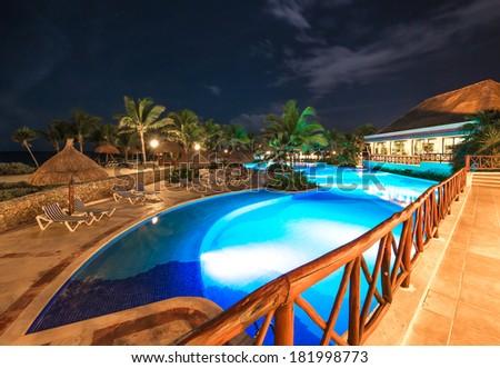 Beach grass umbrella at swimming pool and a promenade at restaurant at luxury caribbean resort at night, dawn time. Bahia Principe, Riviera Maya, Mexico. - stock photo