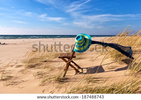 Beach Hat, Scarf and Chair on Beach - stock photo