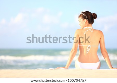 Beach holidays woman enjoying summer sun sitting in sand looking happy at copy space. Beautiful young bikini model. Mixed race Caucasian / Asian Chinese. - stock photo
